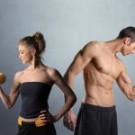 Young man and woman in sport clothes lifting weights