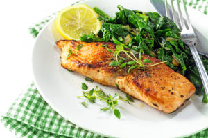 grilled salmon with thyme lemon and spinach on a plate vegetarian low carb dish green white napkin on a white background selected focus narrow depth of field